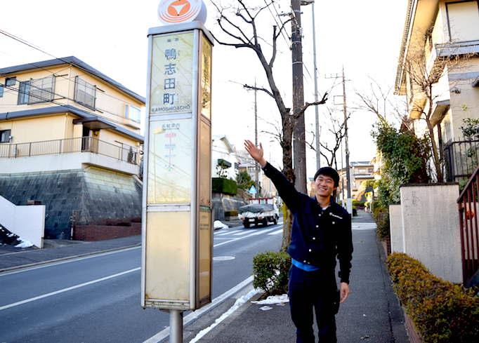 大久保恒産への道順記事におけるバス停を案内する大久保陽介の写真