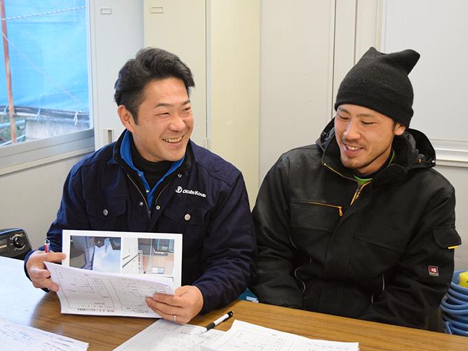 大久保恒産の番頭の仕事紹介記事における小池さんと職人さんの談笑写真