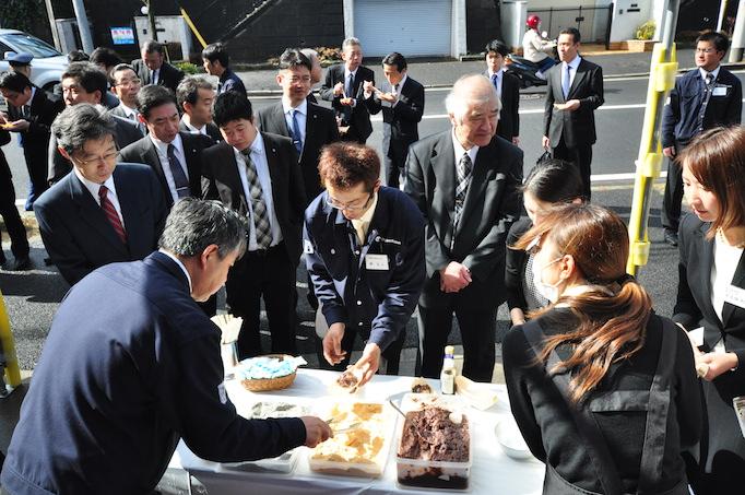 大久保恒産新社屋お披露目会において新卒社員がお餅を来賓の方に配る写真