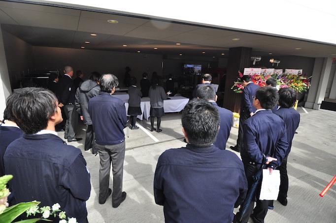 大久保恒産の新社屋お披露目会において大久保恒産社員がお披露目会の様子を見守る写真