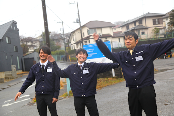 大久保恒産の新社屋お披露目会における新卒社員の駐車場誘導で手を振っている写真