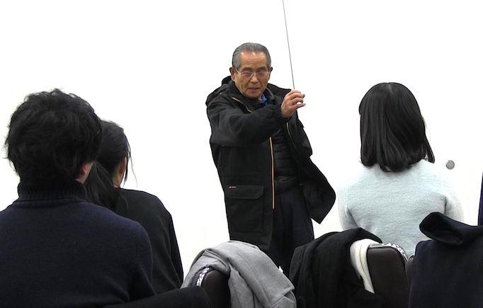 足場職人体感プログラム【HANABI】で参加者の学生に大久保社長がプレゼンをしている写真